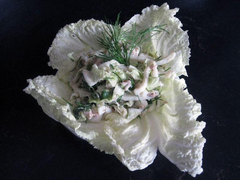 Подавайте салат с кальмарами, разложив порциями на листы капусты