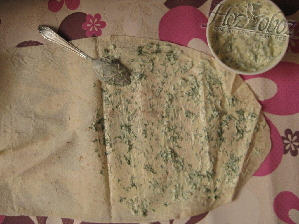 Разверните лист лаваша и намажьте соусом