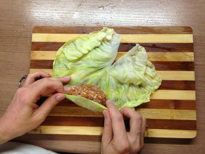 Возьмите лист капусты и покладите на него одну ложку фарша