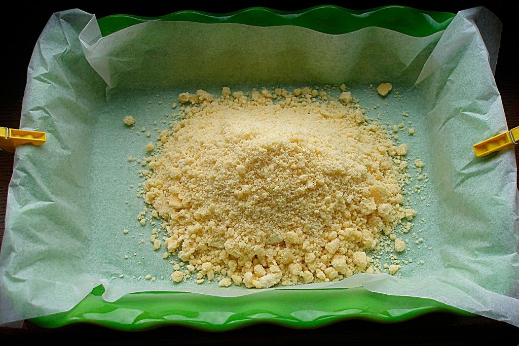 Застелите форму для выпечки пергаментом и выложите половину нашего теста для творожного пирога