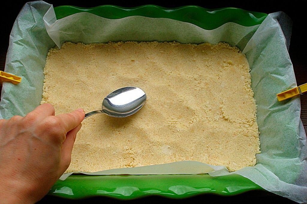 Хорошенько утрамбуйте тесто на дно формы, используя ложку