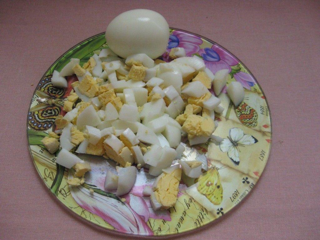 Сварите вкрутую несколько яиц, очистите их от шкарлупы и мелко нарежьте. Яйца пойдут в начинку фаршированных помидоров