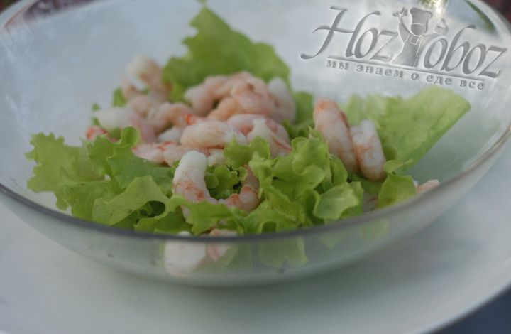 Выкладываем листья салата в тарелку, а сверху креветки