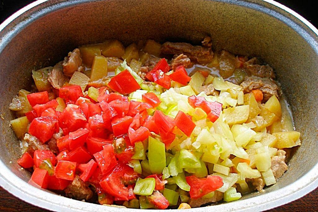 Нарежьте помидор и болгарский перец и также отправьте в бограч