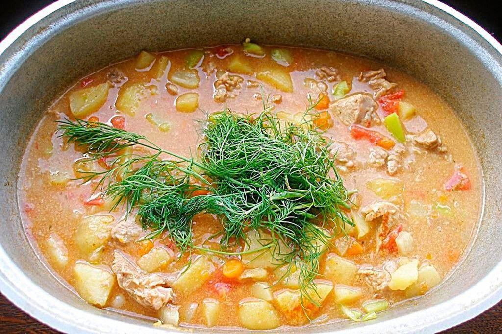Добавляем целую ветку петрушки или укропа и готовим еще минут 15 до полной готовности перца и помидора