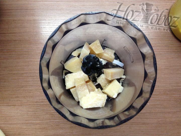 Сыр Пармезан режем небольшими кусочками и помещаем в чашу кухонного комбайна