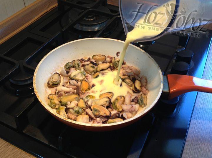 Как только морепродукты поджарятся, необходимо залить их смесью для омлета и накрыть крышкой