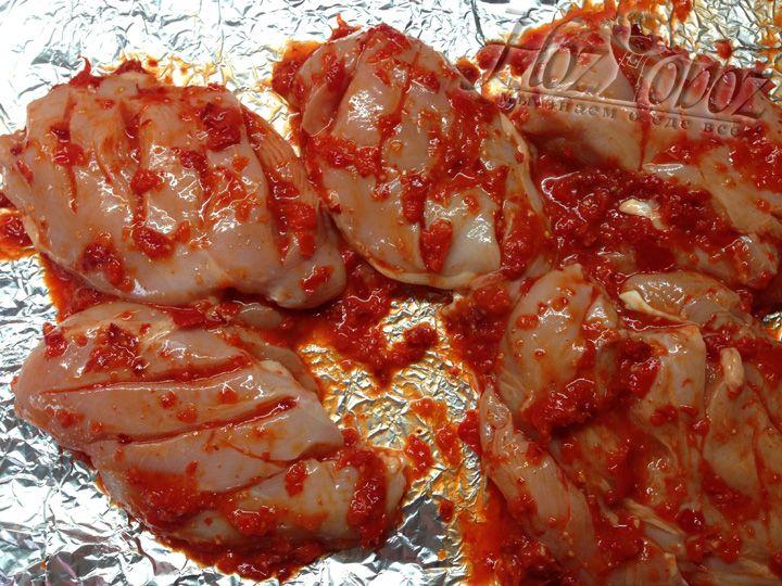 Берем большой кусок фольги, выкладываем на нее курицу и каждый кусок обильно смазываем соусом, не забывая положить его в надрезы