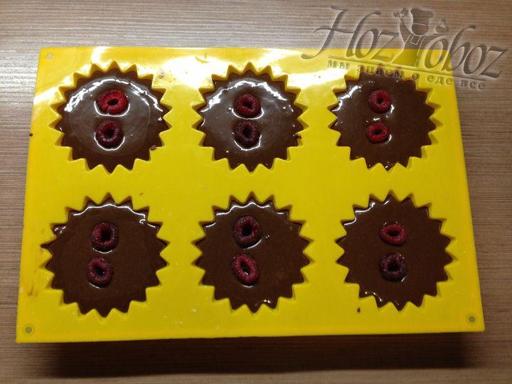 Теперь в каждый кекс положим по 2 малины, как бы утопив их внутрь так, чтобы верхушка осталась на поверхности