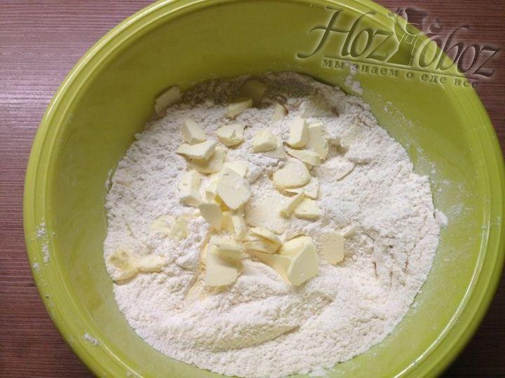 Нарезаем мелкими кусочками охлажденное масло и добавляем в муку