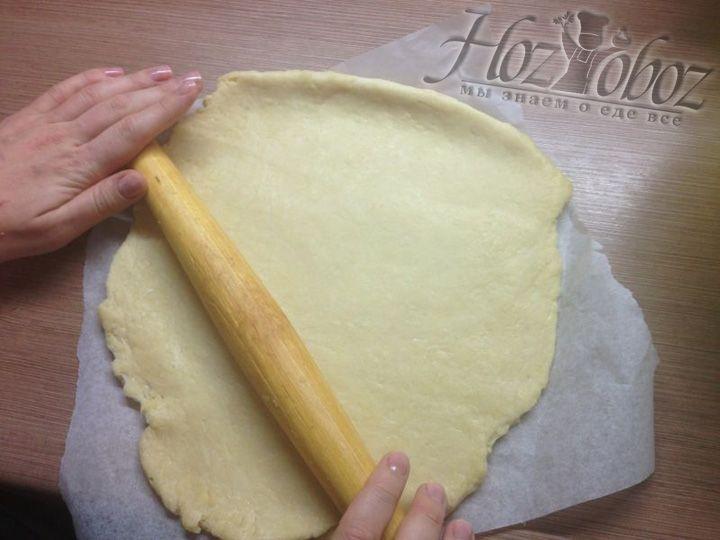 Песочное тесто тем временем уже подошло и его можно начинать раскатывать. Сейчас нам понадобиться 2/3 теста. Выкладываем его на бумагу для выпечки и раскатываем прямо на ней, так будет проще переложить тесто в форму для выпечки