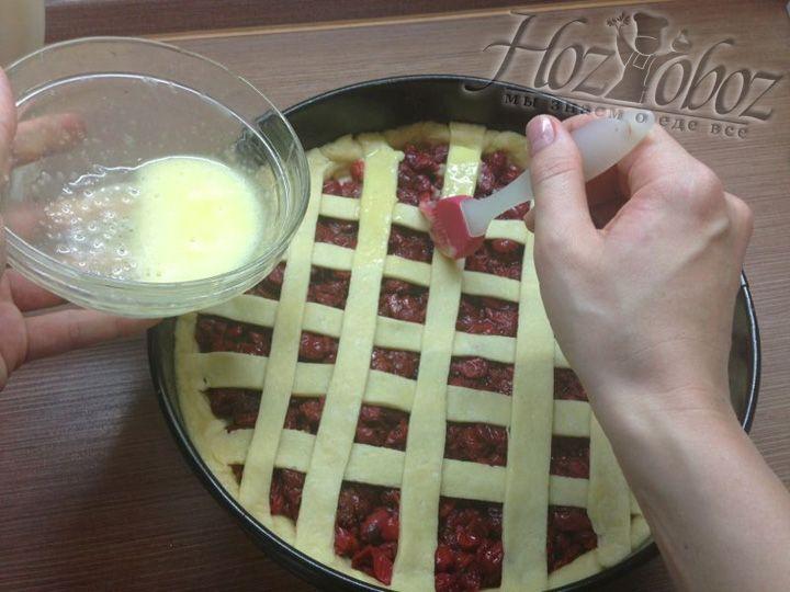 Теперь с помощью венчика смазываем полоски теста на пироге смесью желтка с сахаром