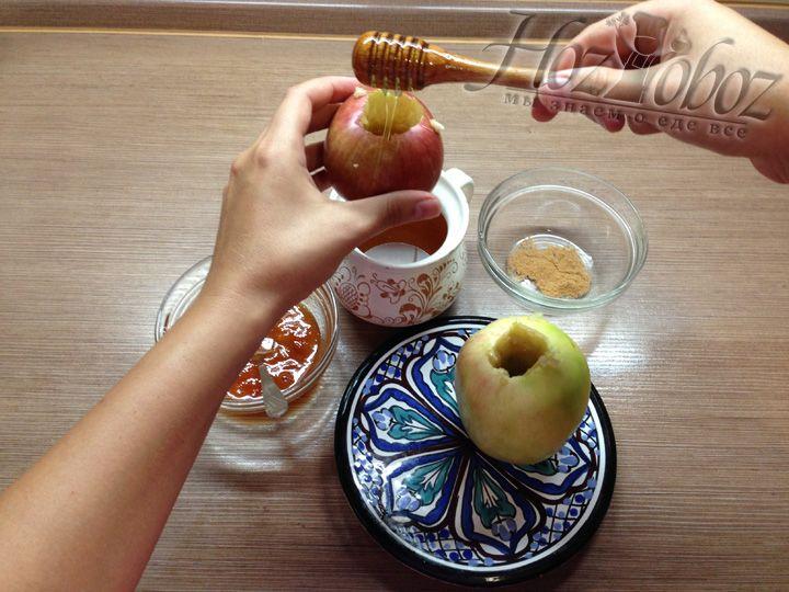 В вычищенную сердцевину яблок заливаем одну ложку меда