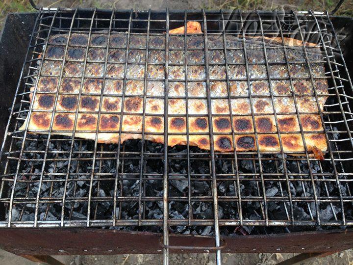Теперь готовим угли, помещаем рыбу в решетку и кладем ее на огонь шкурой вниз. Готовим до тех пор пока шкура основательно не зарумянится, примерно 5-7 минут
