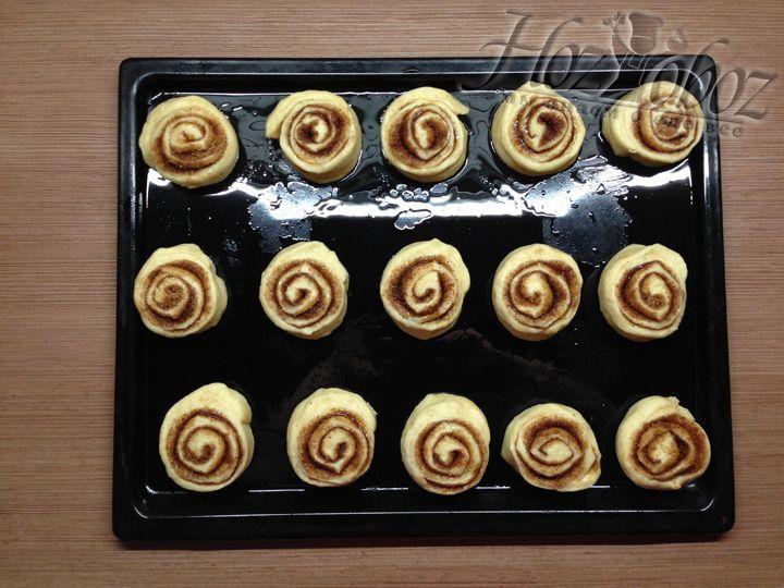 Смазываем противень для выпечки растительным маслом, режем рулет на куски толщиной 5-6 см и выкладываем булочки на лист для выпечки