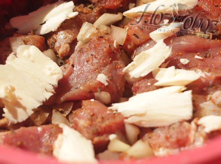 Выложите мясо с луком в сотейник, а сверху разложите небольшие кусочки сливочного масла