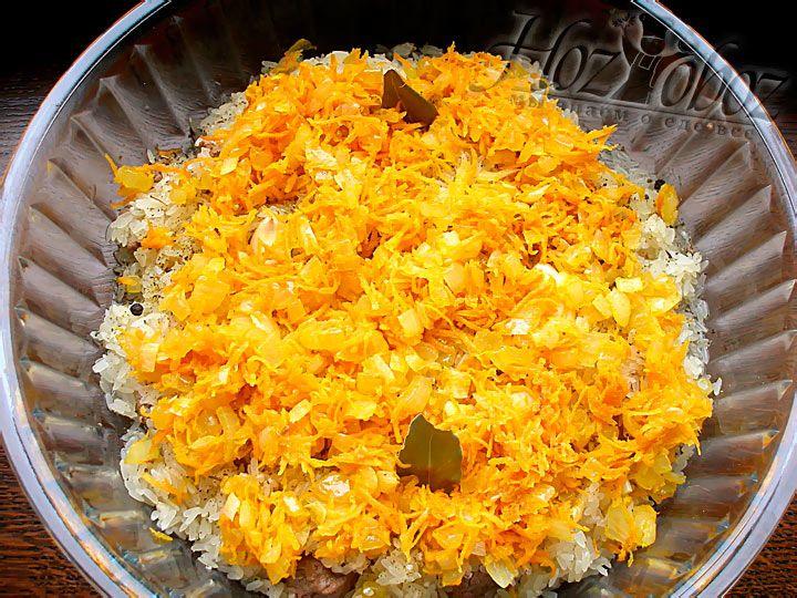 Поверх риса кладем поджаренный лук и морковь. Не забываем посолить, добавить перец горошком и положить лавровый лист