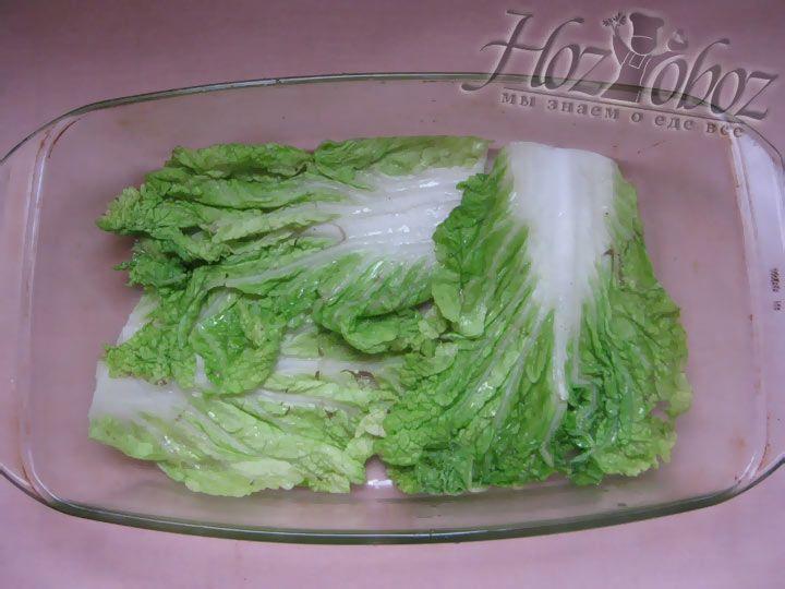 Выложите на дно формы для запекания первый слой листьев капусты