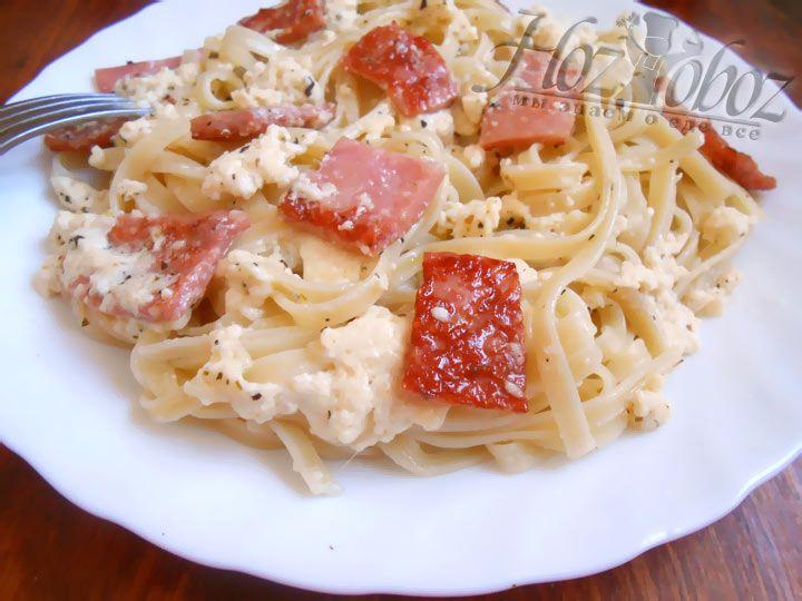 Заправьте макароны сливочно-сырным соусом с ветчиной и подавайте к столу