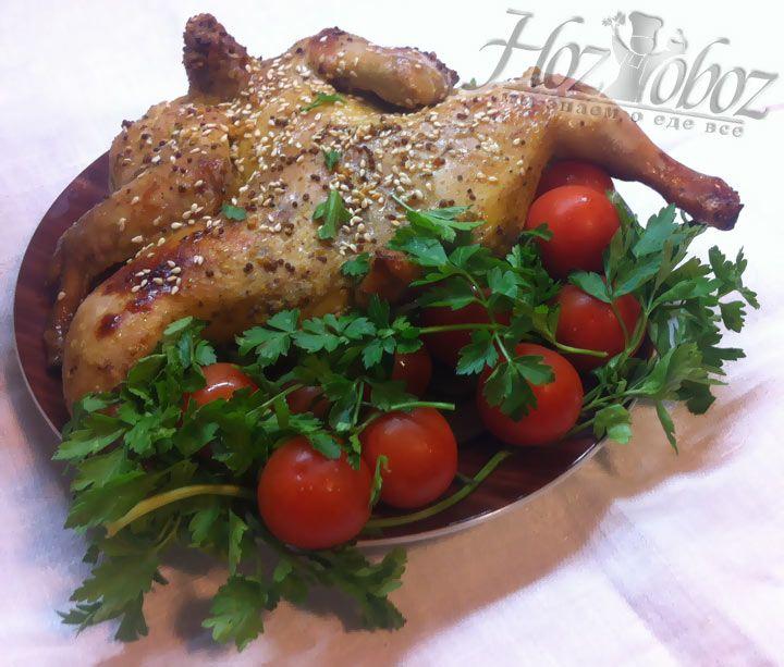 Когда курица хорошо зарумянится, снимаем ее с противня, поливаем соусом, посыпаем кунжутом и подаем с овощами и свежей зеленью