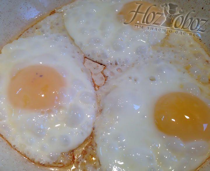 Теперь, накрываем яичницу крышкой и жарим пока желтки сверху не побелеют, но внутри они должны остаться жидкими