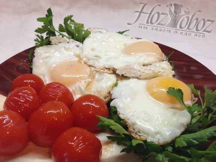 Готовую яичницу с помидорами подают на стол сразу же, посыпав зеленью в прикуску с лавашем