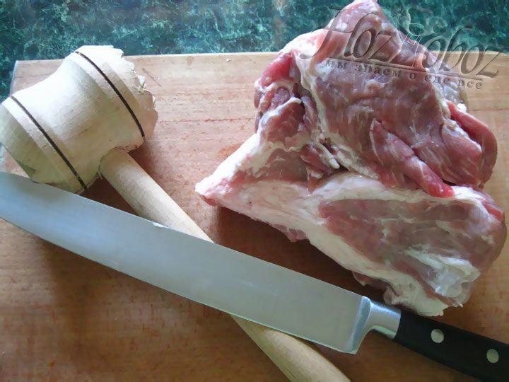 Нарежьте свинину на кусочки и отбейте деревяным молоточком