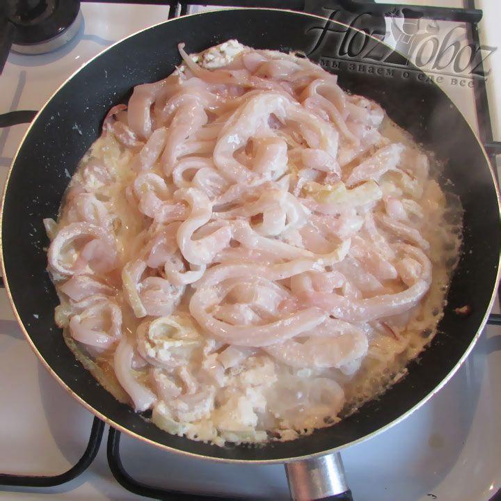 Ставим на огонь сковородку и разогреваем в ней сливочное масло. Как только масло разогреется высыпаем кольца кальмаров, заливаем семтаной и даем потушится, но не более 5 минут