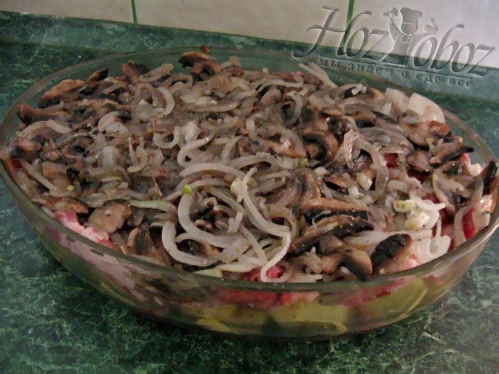 Поверх свинины разложите лук с грибами