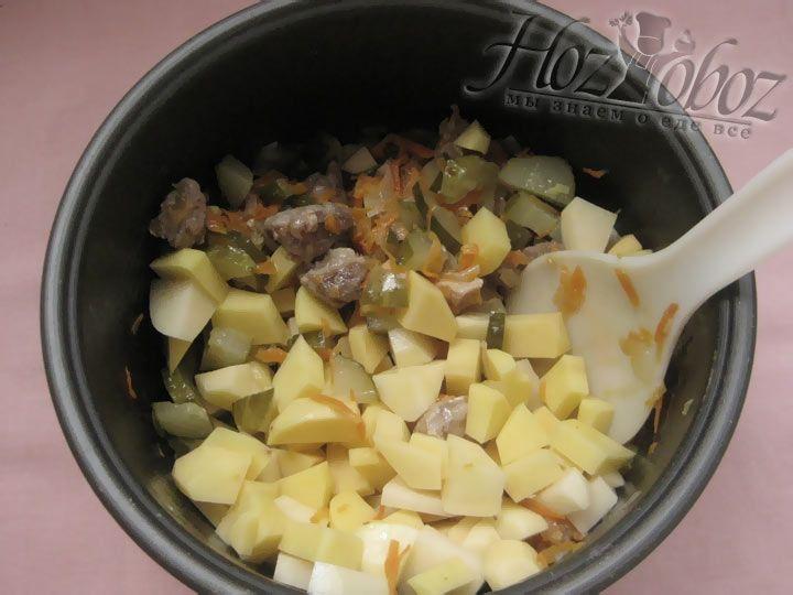 Теперь, когда морковь, лук и мясо потушились, к ним следует добавить рис, соленые огурцы, картошку, а также специи и воду не доходя до максимальной отметки