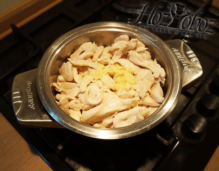 В кастрюлю с курицей добавляем нарезанный мелкими кубиками чеснок