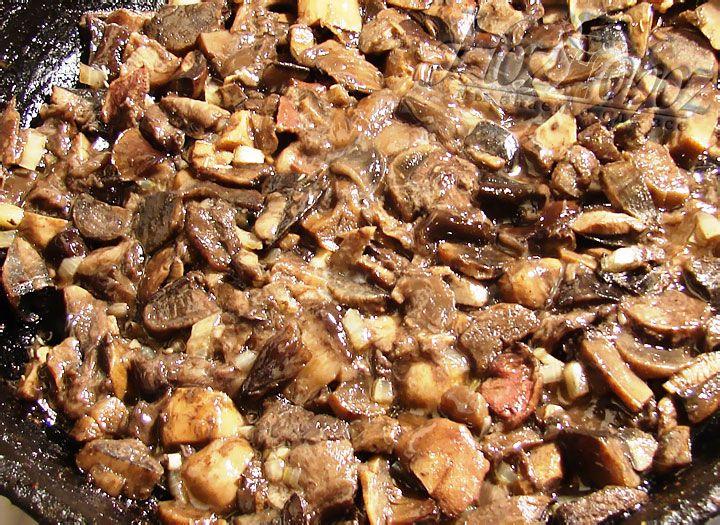 Замоорженные грибы размораживаем на сухой сковороде, затем сливаем воду и тушим их до готовности около 10-15 минут