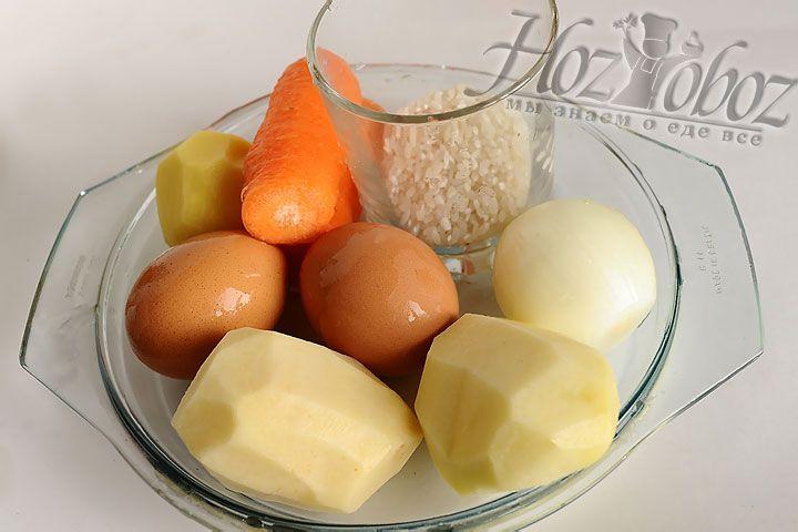Чистим овощи и отвариваем яйца. В кипящий бульон, оставшийся от мяса, закладываем нарезанную кубиками картошку и промытый рис