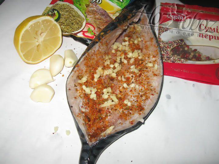 После к рыбе необходимо добавить измельченный чеснок, смесь приправ.