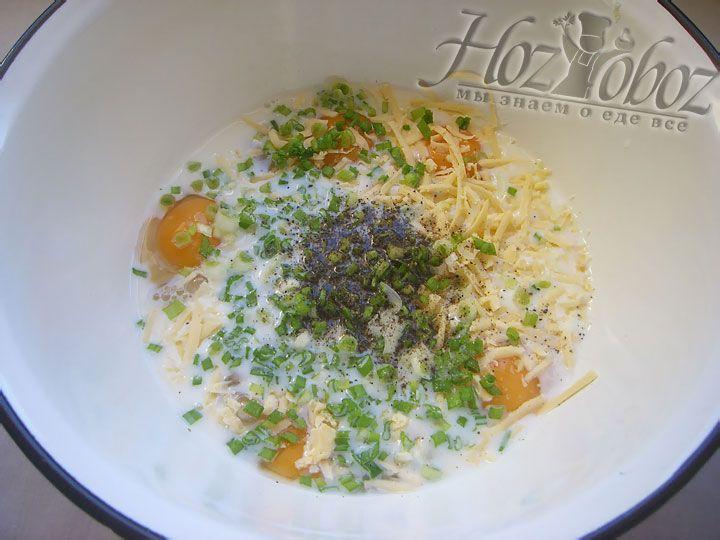 В будущий омлет высыпаем натертый сыр и часть зеленого лука, а затем солим и приправляем его