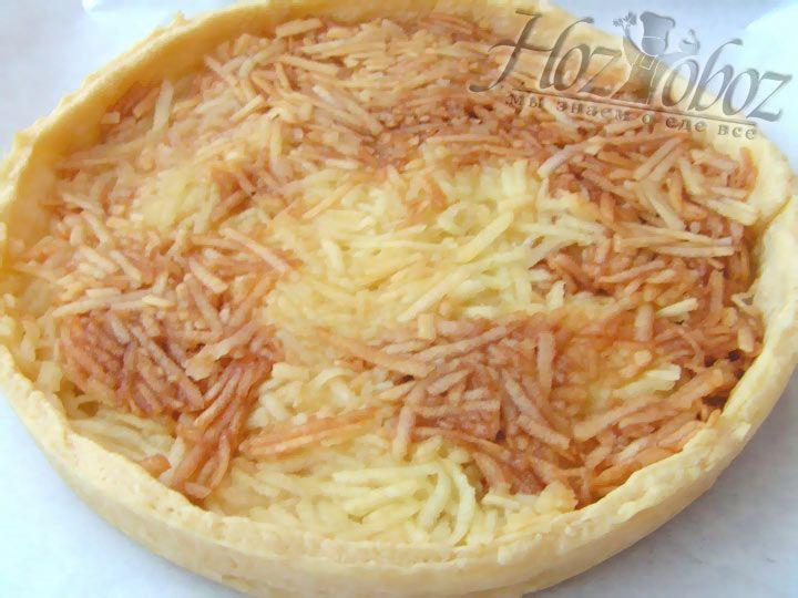 Теперь корж выкладываем на противень выстеленный специальной бумагой для выпечки и наполняем тертыми яблоками