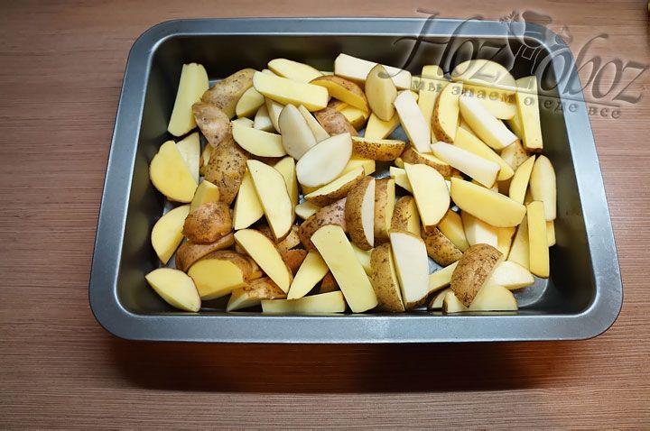 Моем и режем картошку дольками, а затем выкладываем в противень
