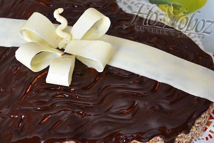 Затем вынимаем торт и сооружаем шоколадный бант. Для этого снимаем полоски трафарета и быстро помещаем бант на сердце, чтобы он не успел растаять