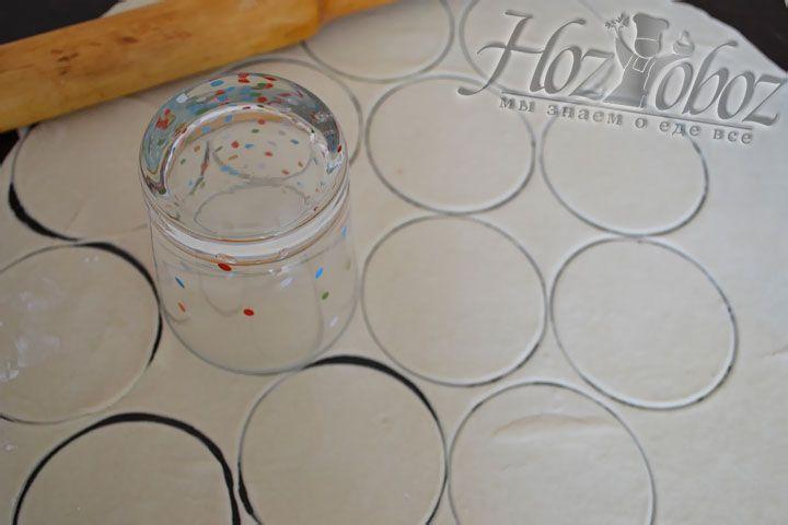 Теперь тесто надо разделить на две равные части и каждую по очереди раскатать в тонкий корж, а затем стаканом выдавливаем заготовки для вареников