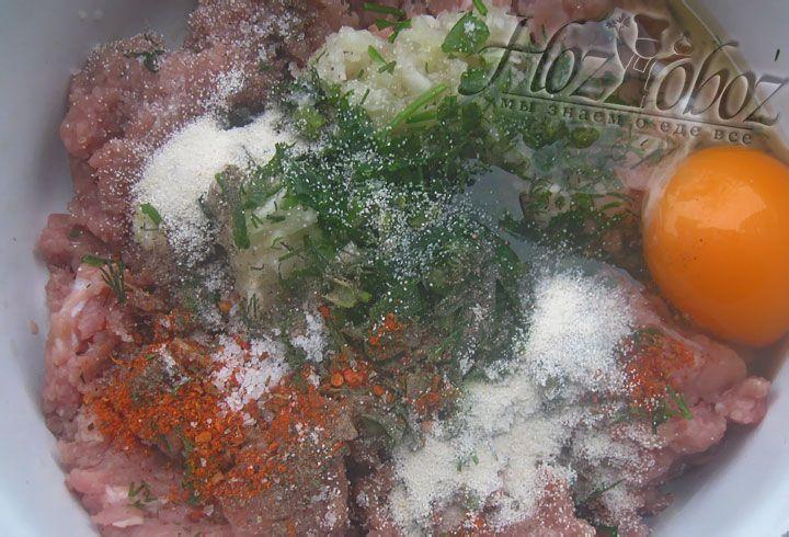 В готовый фарш добавляем лук, яйца, соль, специи, а также зелень, манную крупу и несколько ложек воды