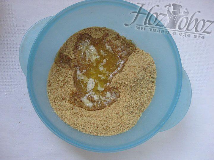 Помещаем на водяную баню сливочное масло и когда оно растопится тщательно смешиваем с крошкой из печенья