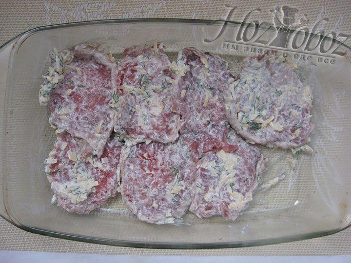 Форму для запекания слегка смазываем растительным маслом и выкладываем в нее кусочки запанированного мяса. Если остался кляр, его можно залить на мясо