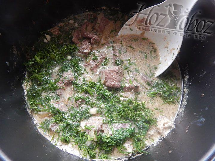 Примерно за 10 минут до окончания приготовления высыпаем в емкость мультиварки измельченный чеснок, лавровый лист и зелень