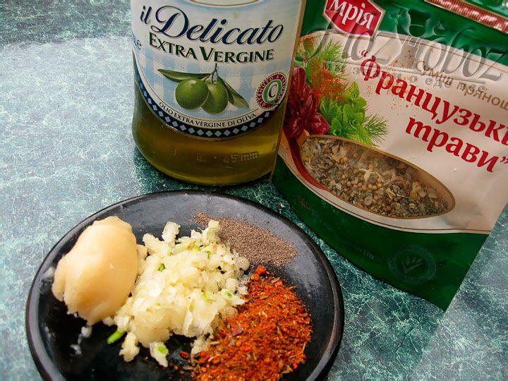 Теперь приготовим соус для рульки. Выдавим несколько зубчиков чеснока и смешаем с черным и красным перцем, французскими травами, чайной ложкой меда и несколько ложечек оливкового масла