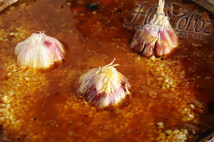 А теперь перекладываем рис и три головки чеснока в казан. Немного разровняйте рис так чтобы его покрыла вода, она кстати не должна выкипать быстро, если это происходит добавляйте постепенно кипяток. Как только вода выкипит почти вся, а рис останется еще немного твердым - убирайте казан с огня и накрывайте крышкой. Рис дойдет примерно за 15 минут