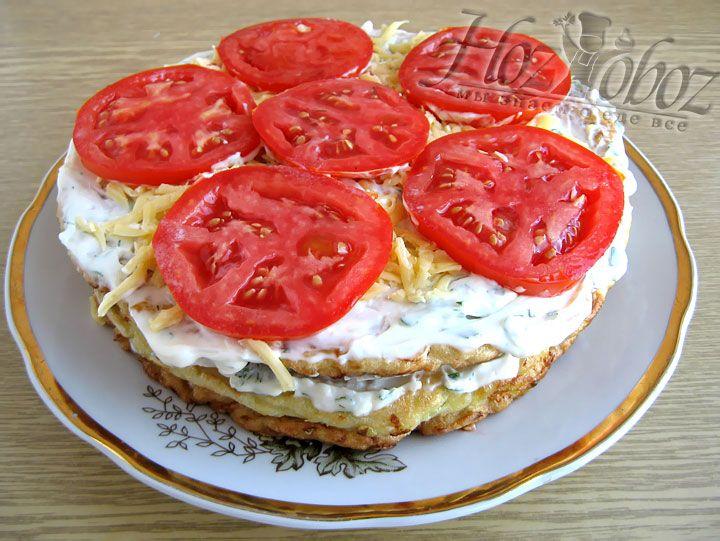 Теперь кладем последний корж, промазываем его кремом, посыпаем сыром и только потом укладываем помидоры в качестве украшения