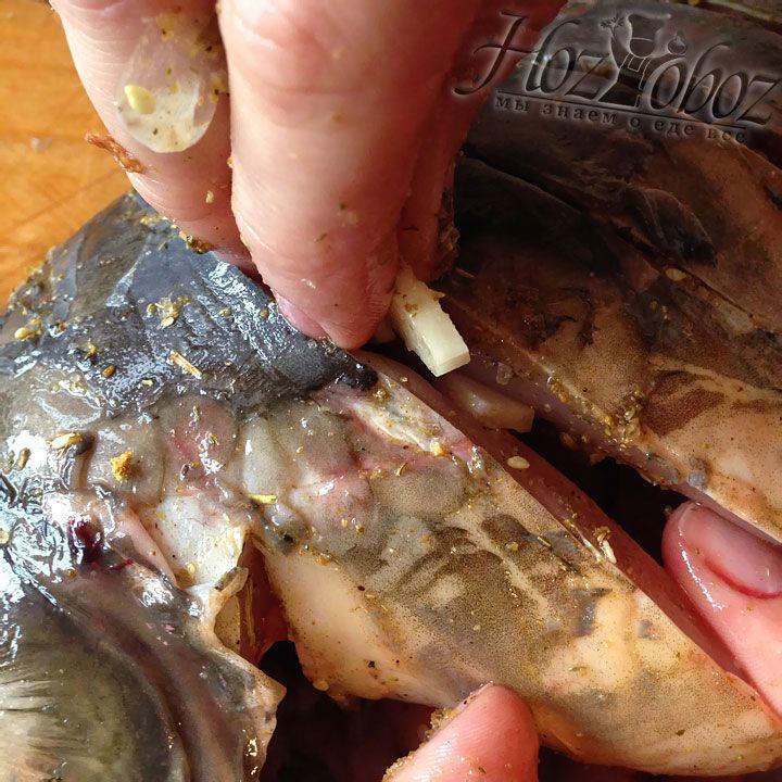 Нарезанный лук и чеснок закладываем в надрезы сделанные на тушках карпа
