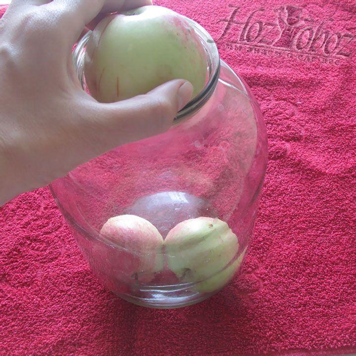 В трехлитровую стерильную банку до половины объема плотно укладываем яблоки