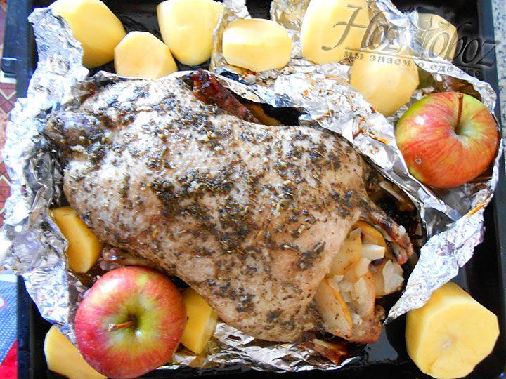 Когда внутри утка будет готова и не останется сукровицы, откроем фольгу и выложим вокруг птицы картофель и яблоки. В таком виде отправим утку с гарниром обратно в духовку еще минут на 40