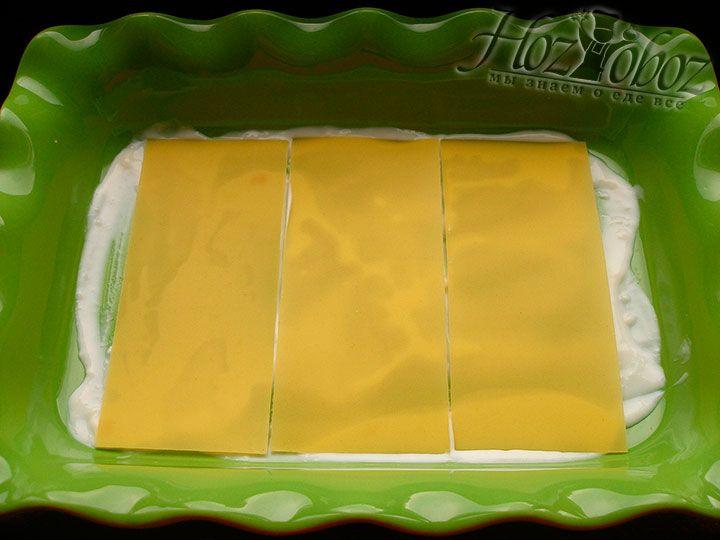 Формируем лазанью: на дно формы выкладываем пару ложек соуса бешамель и накрываем его сырыми листами для лазаньи